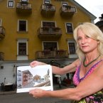 The owner of the hotel Gruener Baum (Green Tree) Monika Wenger shows a drawing which Chinese architects made of her hotel in Hallstatt, Upper Austria (she is standing outside the original). Image: AP Photo/Kerstin Joensson