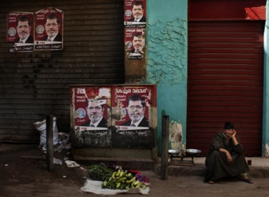 An Egyptian street vendor awaits customers in Cairo by campaign posters for Morsi.