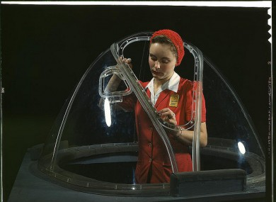 This girl in a glass house is putting finishing touches on the bombardier nose section of a B-17F navy bomber at Long Beach in California.