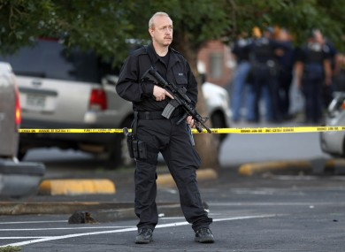 A SWAT team officer stands watch near an apartment house where the suspect in a shooting at a movie theatre lived in Aurora