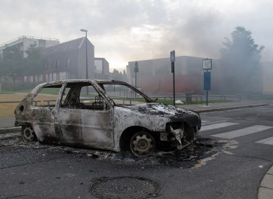 The shell of a burnt out car is seen in a neighborhood of Amiens