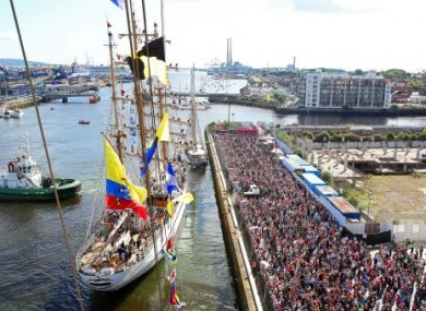 Crowds watch the ships as they sail out of Dublin Harbour on Sunday.