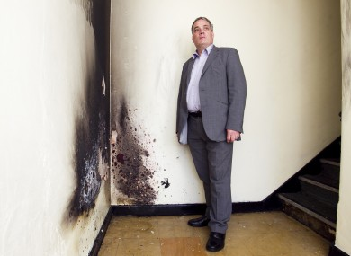 Aengus O Snodaigh beside the damage caused by the petrol bomb in his constituency office hallway today