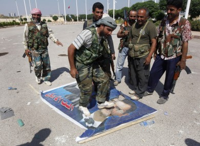 A Free Syrian Army fighter from the Al-Faruk brigade, center, steps on a portrait of Syrian President Bashar Assad, at the Tal Abyad, a Turkish-Syrian border crossing captured by the rebels earlier in the week