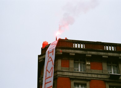A flare being lit on a city centre rooftop during today's protest