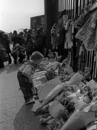 A boy adds a floral tribute at Anfield's Shankly Gates in remembrance of those who lost their lives.