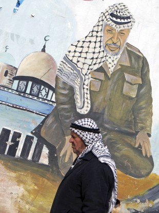 An elderly Palestinian walks next to a mural depicting Yasser Arafat, in the northern West Bank village of Kabatyeh.