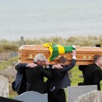 The coffin carrying the remains of the Kerry GAA legend is carried by his son Pádraig Óg (centre) and other family members to his graveside.