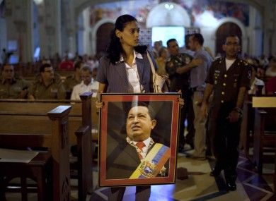A woman carries an image of Hugo Chavez before a mass in support of him in Cuba