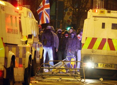 Loyalist protestors carrying Union flags clash with police outside the City Hall in Belfast on Monday evening.