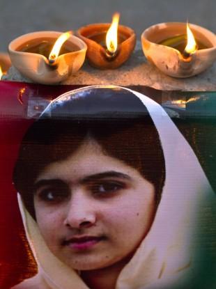 Clay lamps burn near a poster of 15-year-old Malala Yousufzai in Islamabad.