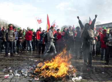 Union members light a fire during a demonstration outside an EU summit in Brussels on Thursday
