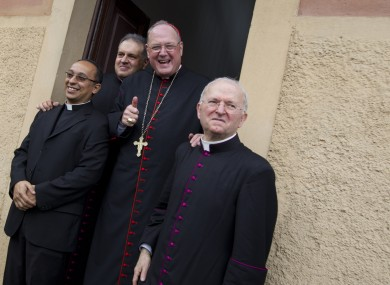 New York Archbishop Cardinal Timothy Dolan, second from right, poses for a photo as he leaves the Saint Mary of Guadalupe church after celebrating mass, in Rome, yesterday.