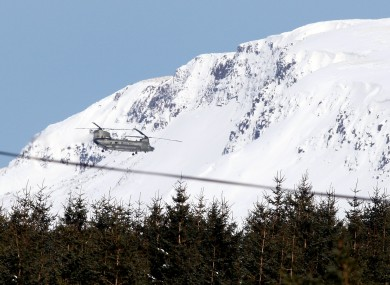 A Royal Air Force helicopter, in the Glens of Antrim, which has started dropping feed to thousands of farm animals.