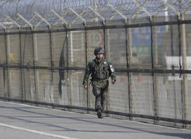 A South Korean army soldier walks along the military wire fences near a border town that has separated the two Koreas since the Korean War