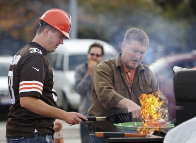 Cleveland Browns fan Kevin Vassar cooks some burgers on the grill.