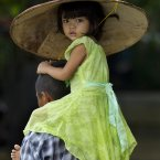 A child is carried by an adult in Khanaung Chaung Wa village, southeast of Yangon Myanmar, Wednesday. (AP Photo/Gemunu Amarasinghe)