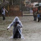 An Indian girl wearing a raincoat walks on a waterlogged street as it rains in Mumbai. (AP Photo/Rajanish Kakade)