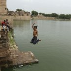 An Indian boy jumps into a water tank reservoir that got filled after monsoon rains in Ahmadabad, India. The annual monsoon season from June to October brings rains that are vital to agriculture in India. (AP Photo/Ajit Solanki)