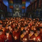 Novice Buddhist monks offer prayers for peace at the Tergar Monastery, the site of an explosion, in Bodhgaya, about 130 kilometers (80 miles) south of Patna, the capital of the eastern Indian state of Bihar. One man has been detained and sketches of two others have been prepared as investigators searched for clues Monday into a series of blasts at some of Buddhism's holiest sites in Bodhgaya. (AP Photo/Manish Bhandari)