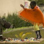 Children lay down stones with well wishes in support of former South African President Nelson Mandela in front of his house in Johannesburg, South Africa, Saturday. (AP Photo/Markus Schreiber)