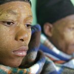 A Xhosa boy covered with a blanket take part in a traditional Xhosa male circumcision ceremony into manhood near the home of former South African president Nelson Mandela in Qunu, South Africa. (AP Photo/Schalk van Zuydam)
