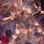 Revelers are sprayed with water thrown from balconies during the launch of the 'Chupinazo' rocket, to celebrate the official opening of the 2013 San Fermin fiestas in Pamplona, Spain. Revelers from around the world kick off the San Fermin festival with a messy party in the Pamplona town square, one day before the first of eight days of the running of the bulls glorified by Ernest Hemingway's 1926 novel 'The Sun Also Rises'. (AP Photo/Daniel Ochoa de Olza)