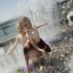 Wesley Traeger, 3, left, and his brother Alex, 5, right, both from Washington DC, run through the water fountains to cool off at the Yards Park, near the Washington Nationals baseball stadium, where temperatures were in the mid-90s (F) in Washington. (AP Photo/Pablo Martinez Monsivais)
