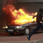 A Loyalist protester runs past a burning car during the riots. (AP Photo/Peter Morrison)