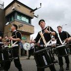 Sinn Fein supporters parade pass Castlederg PSNI station. Pic: Julien Behal/PA Wire
