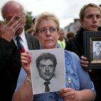 Loyalist protestors hold pictures of IRA victims. Pic: Julien Behal/PA Wire