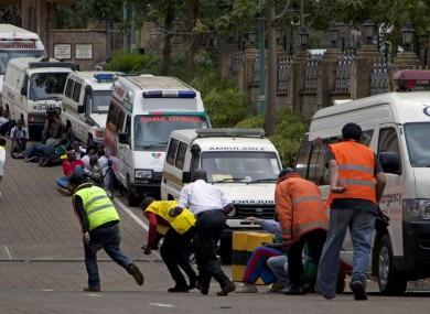 Paramedics take cover beside parked ambulances outside the Westgate mall