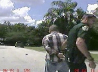 In this image made from dash-cam video and released by the Lake Mary (Florida) Police, George Zimmerman is detained by officers on Monday, 9 September, 2013 after Police in central Florida were called via 911 by Shellie Zimmerman saying her estranged husband was in his truck and threatening her and her father with a gun.