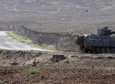 A Turkish tank stands near a fence of the Turkish-Syrian border.