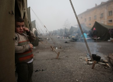 5-yrea-old Mohamed Abdo, from Hasaka, Syria, stands in front of unheated tent at the Harmanli camp