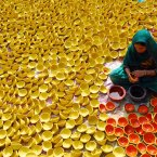 An Indian potter paints earthen lamps ahead of Diwali, or the Hindu festival of lights, in Amritsar, India.<span class=