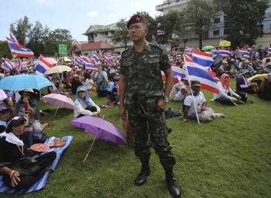 A Thai soldier stands as anti-government protesters sit at the Royal Thai Army compound in Bangkok