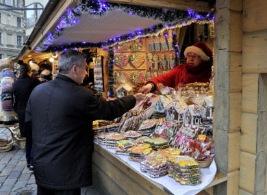 A man buys souvenirs at a Christmas market in Riga on Friday.