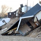 Houses collapsed following a tidal surge along the cliff edge on Hemsby beach in Norfolk, England.<span class=