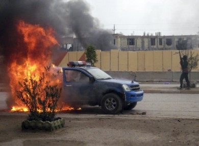 An al-Qaeda fighter stands guard after setting fire to an Iraqi police truck in Fallujah.