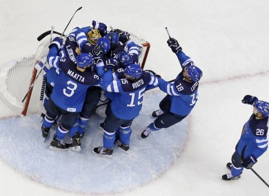Team Finland celebrates their 3-1 win over Russia in a men's quarterfinal ice hockey game.