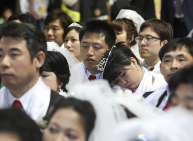 A newly-married couple takes a nap in a mass wedding ceremony at the CheongShim Peace World Center in Gapyeong, South Korea.