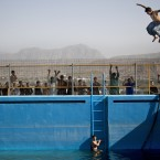 An Afghan man jumps from a diving board into a swimming pool on a hill overlooking Kabul, Afghanistan.<span class=