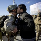 An Afghan special forces soldier, left, is kissed by an Afghan man after the commandos took over control of an election office.<span class=