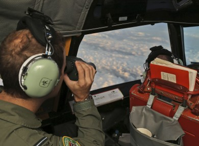 Flight Officer Stuart Doubleday uses binoculars on board a Royal Australian Air Force AP-3C Orion to scan for debris or wreckage of missing Malaysian Airlines flight.