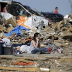 A girl talks on a cell phone as she sits in the rubble of her home that was destroyed by a tornado .<span class=