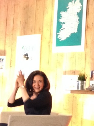 Sheryl Sandberg applauds a