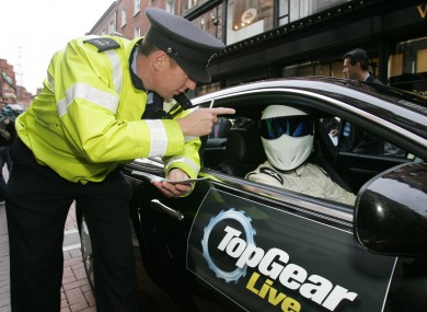 A member of the Gardaí cautioning the Stig.