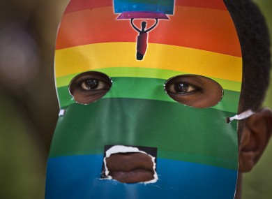 A Kenyan man wears a mask to preserve his anonymity as they stage a rare protest against Ugandan's laws on sexuality.
