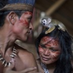 A small monkey sits atop the head of a woman in the Tatuyo indigenous community near Manaus, Brazil. <span class=